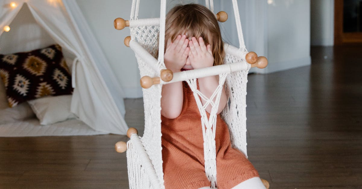 A little girl sitting on a wooden table