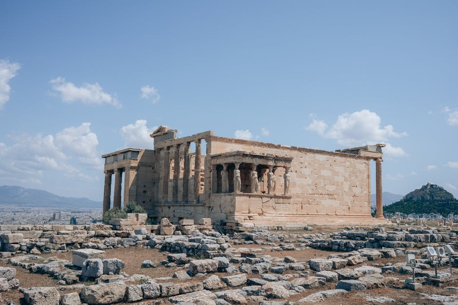A large stone building with Erechtheion in the background